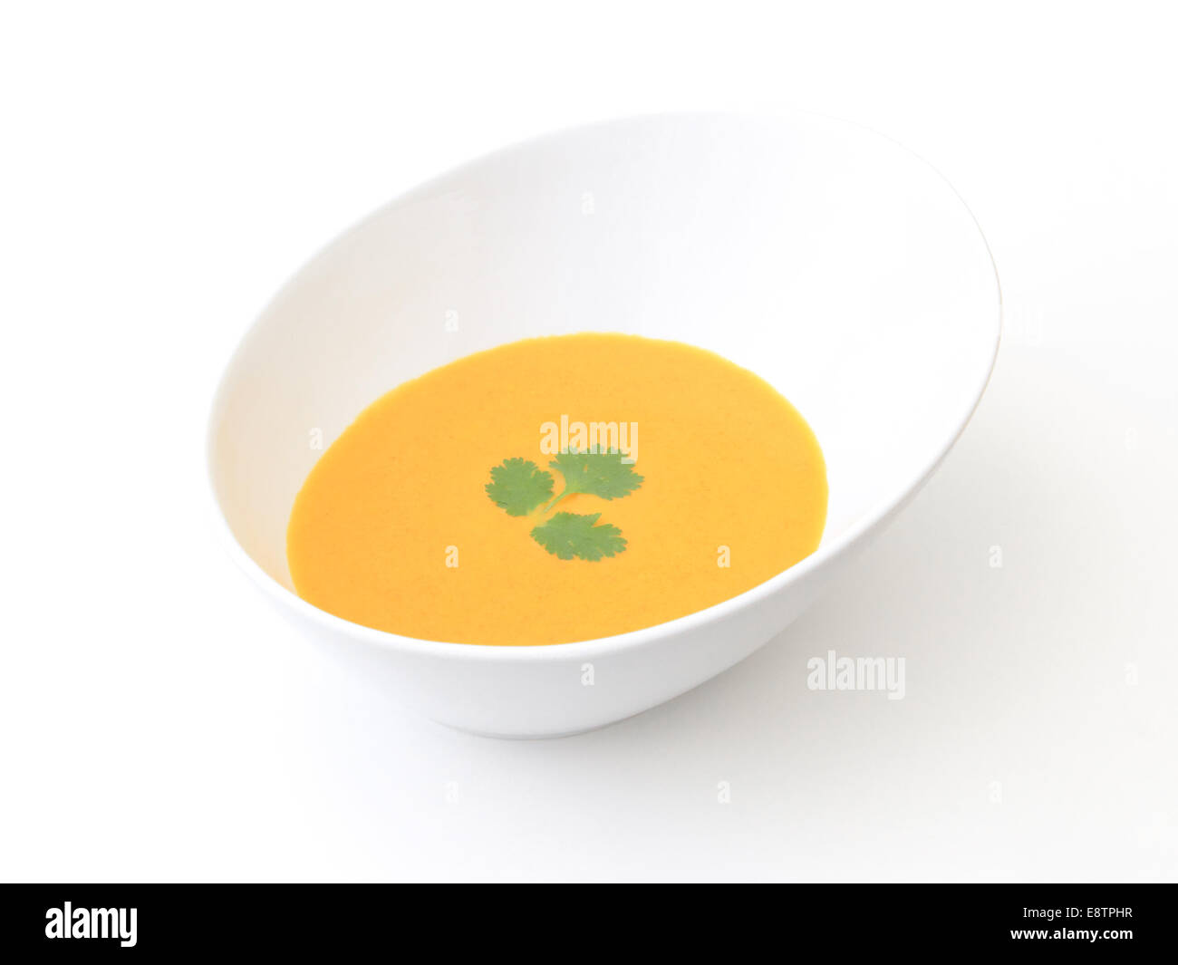 A bowl of carrot soup isolated on a white background. Stock Photo