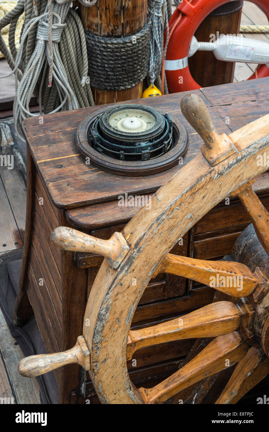 Ships compass and steering wheel on deck of an old Tall Ship. - Stock Image