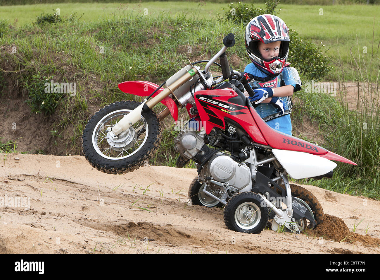 Young boy standing behind his dirt bike.  It is stuck in the sand. - Stock Image