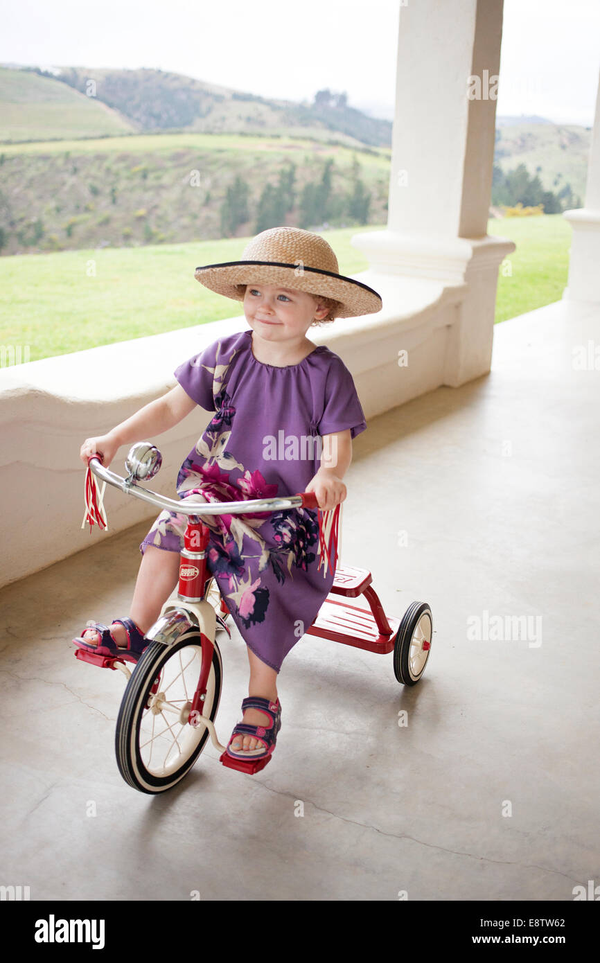 Pretty three year old in a hat on a tricycle - Stock Image