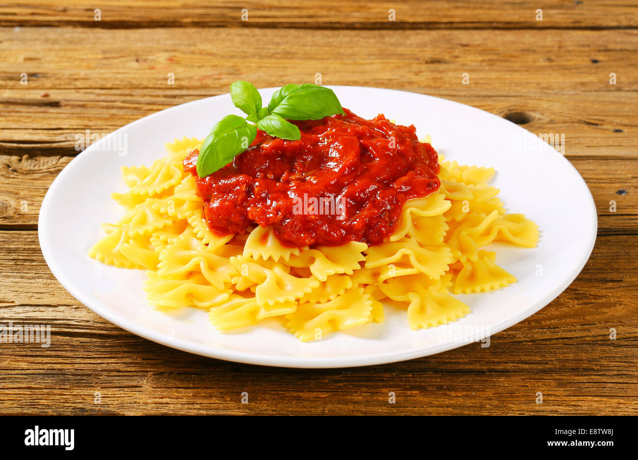Bow-tie pasta with thick tomato sauce - Stock Image