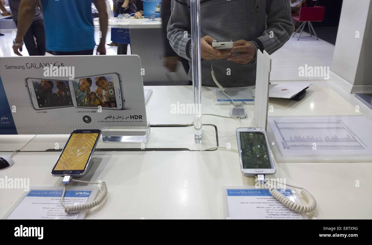 Tehran, Iran. 14th Oct, 2014. October 14, 2014 - Tehran, Iran - An Iranian customer tries out a Samsung Galaxy S5 smartphone at a Samsung store in a multimedia and computer shopping center in southern Tehran. Morteza Nikoubazl/ZUMAPRESS © Morteza Nikoubazl/ZUMA Wire/Alamy Live News Stock Photo