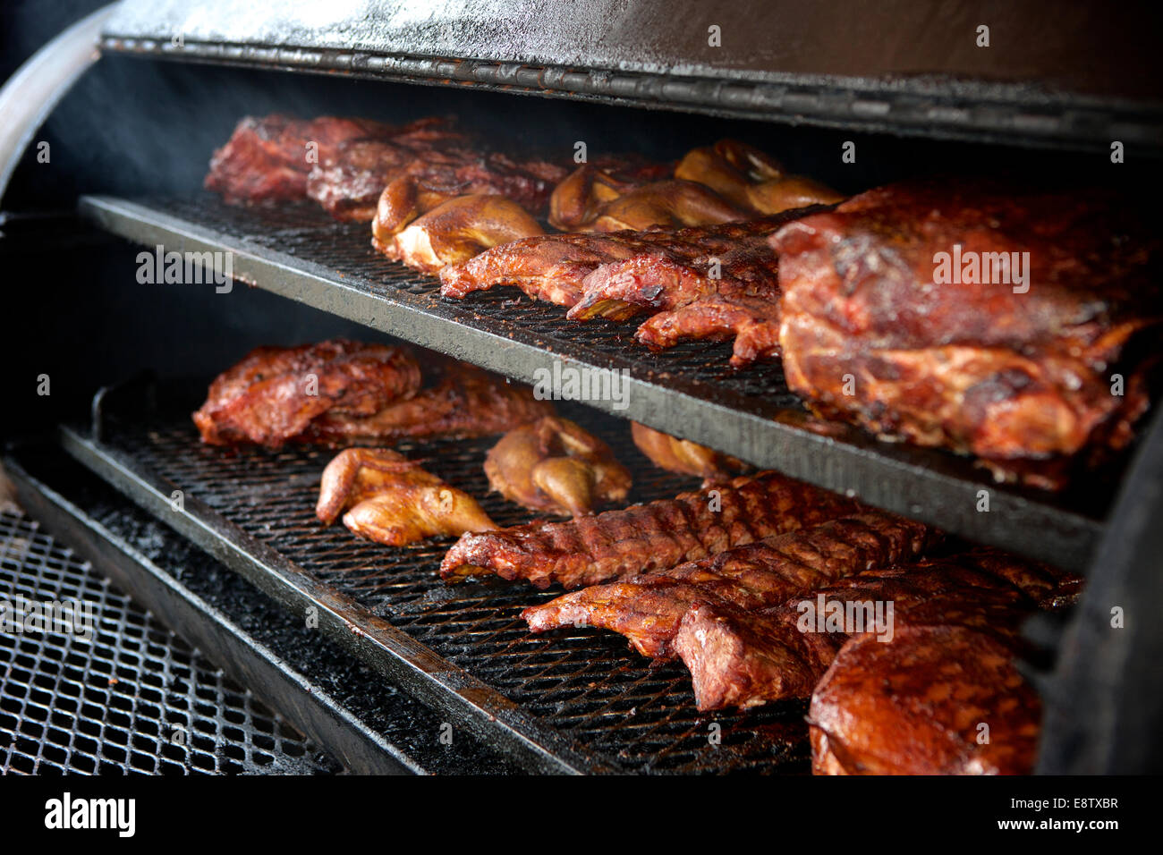 Chicken, Beef Brisket, and Pork Ribs in the smoker. - Stock Image