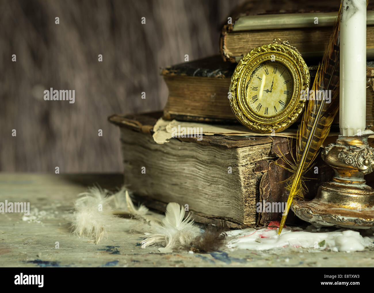 Old books, antique clock, candle in a candlestick and quill on wooden background. Vintage postcard. - Stock Image