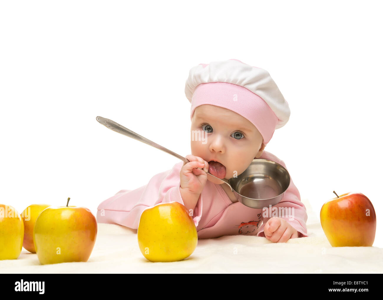 Little baby is looking into the camera and apple on the white background - Stock Image