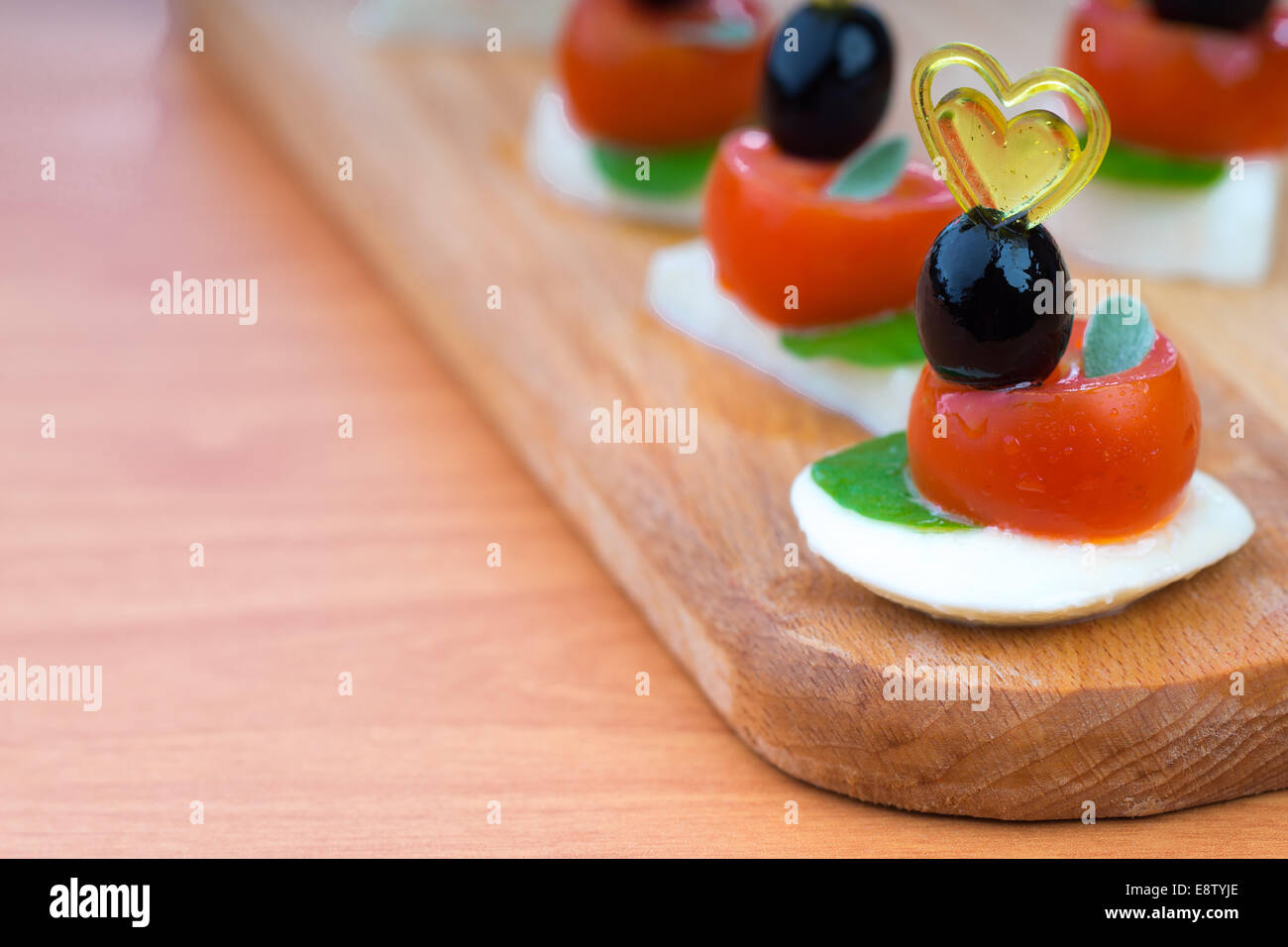 Simple snack canape with tomato, mozzarella and basil close-up on wooden background - Stock Image
