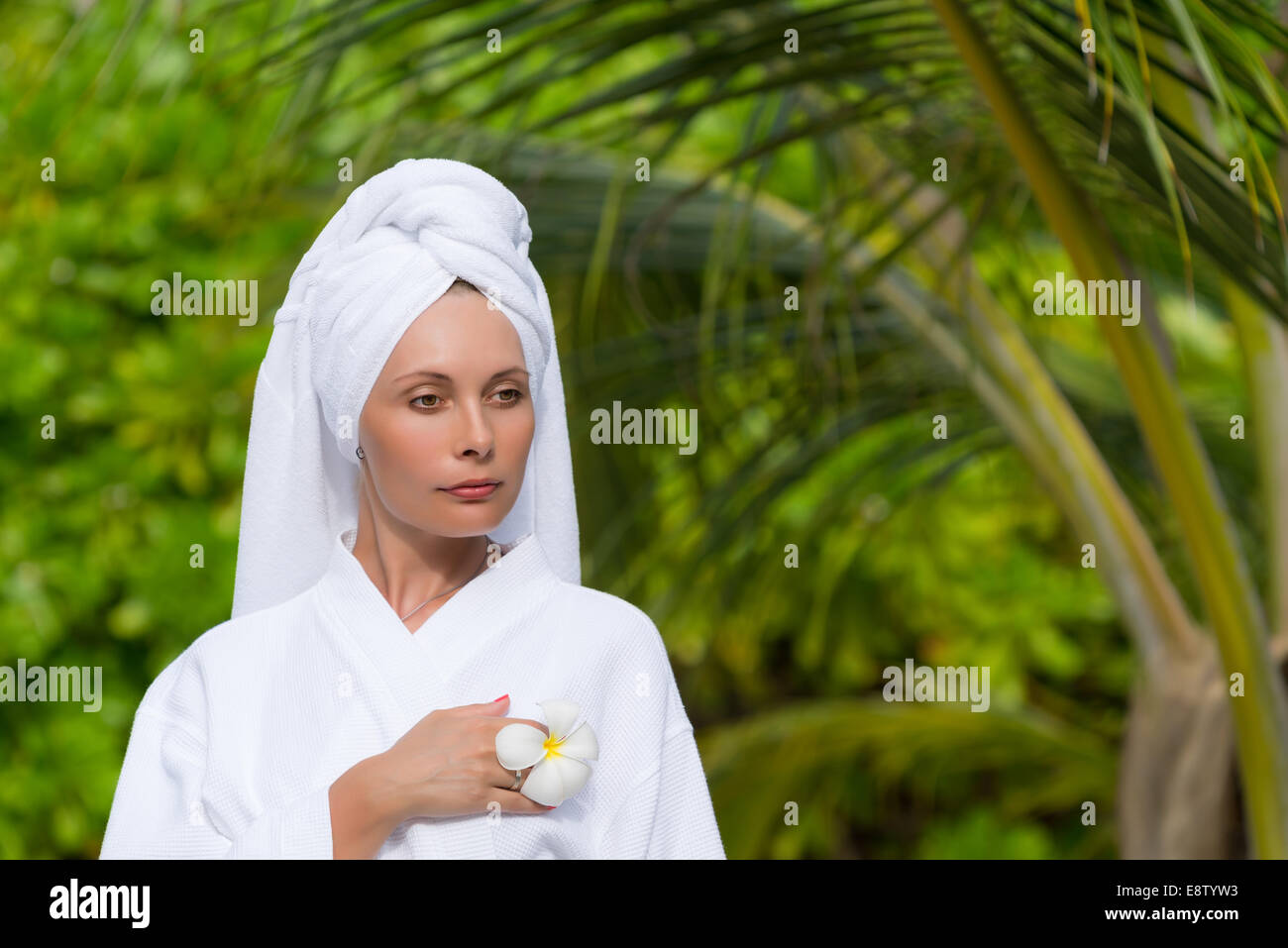health, spa and beauty concept - beautiful woman in towel - Stock Image
