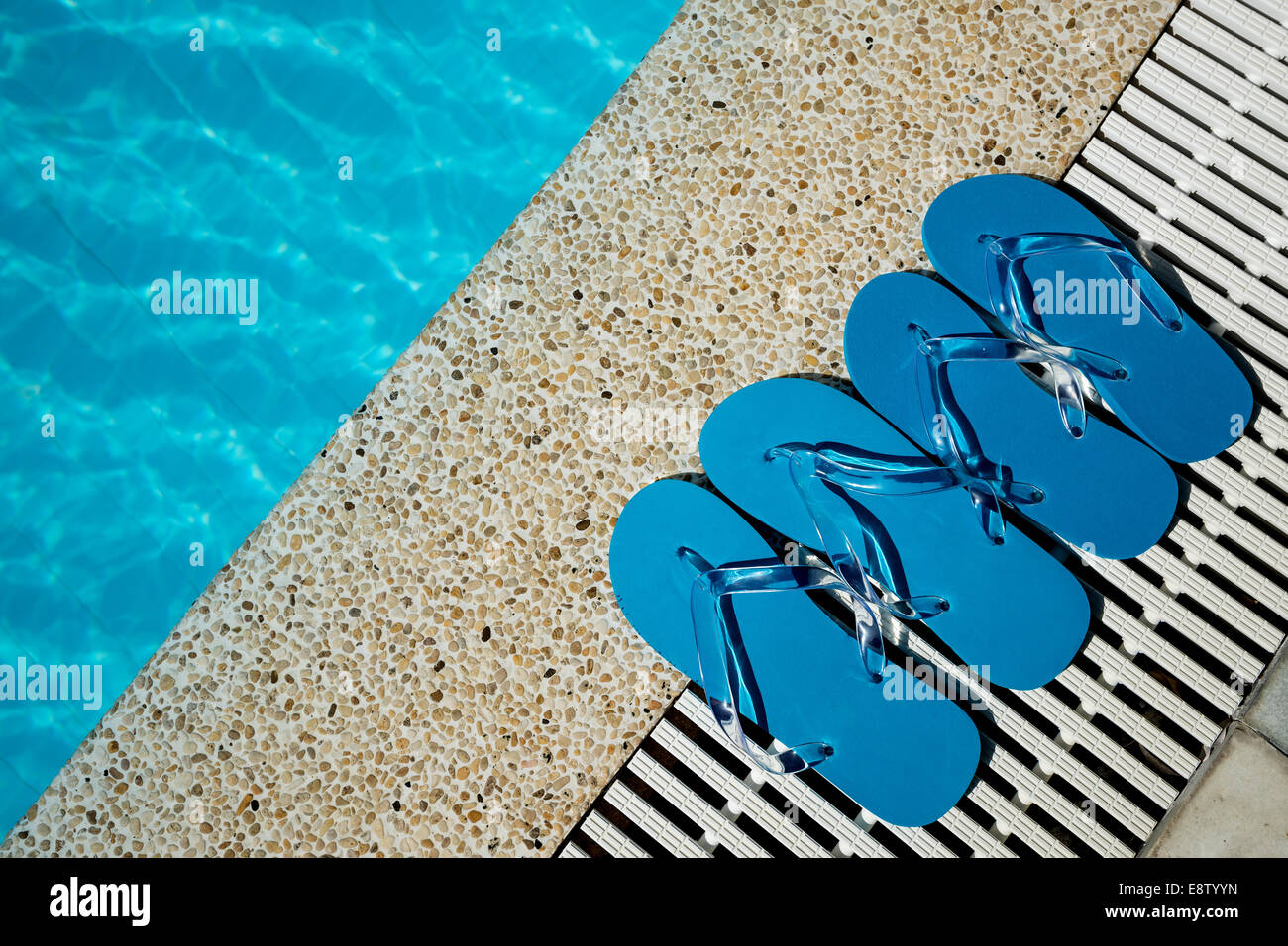 Flip Flop on Wood Floor pool edge with surface of water background - Stock Image