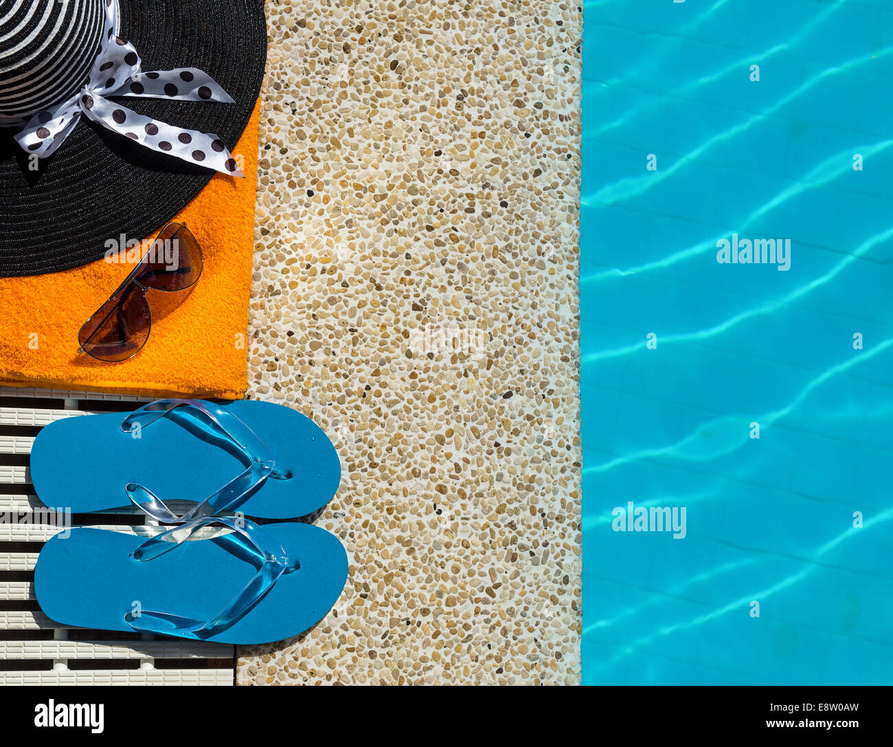 Flip Flop, towel, hat on pool edge with surface of water background - Stock Image