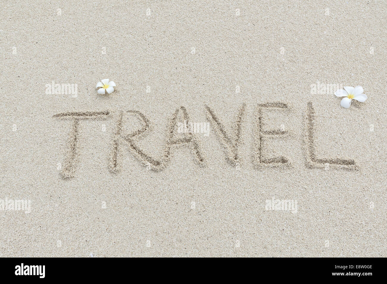 Travel written on the sandy beach - Stock Image