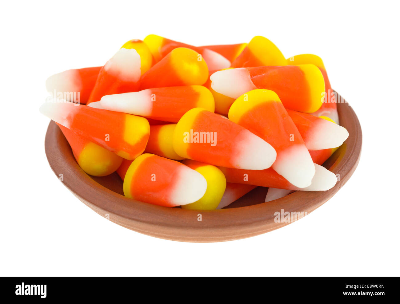 Halloween candy corn kernels in a small bowl on a white background. - Stock Image