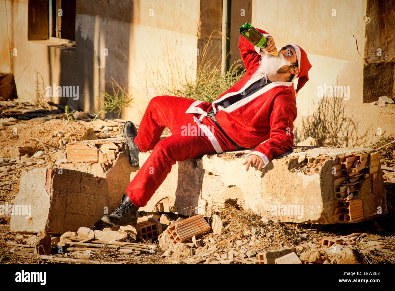A stressed out Santa indulging in a bottle of champagne - Stock Image