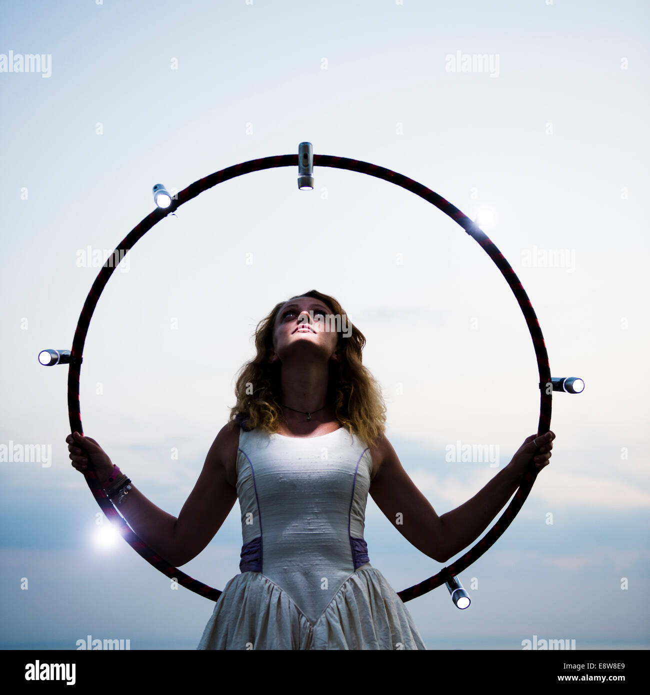 A woman in a wedding dress holding a hula hoop  with lights - Stock Image