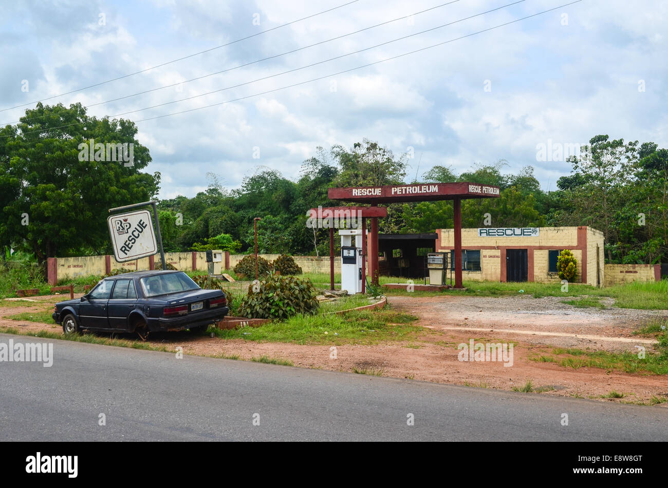 An abandoned gas station in south-west Nigeria reading 'RESCUE PETROLEUM' and a car wreck - Stock Image