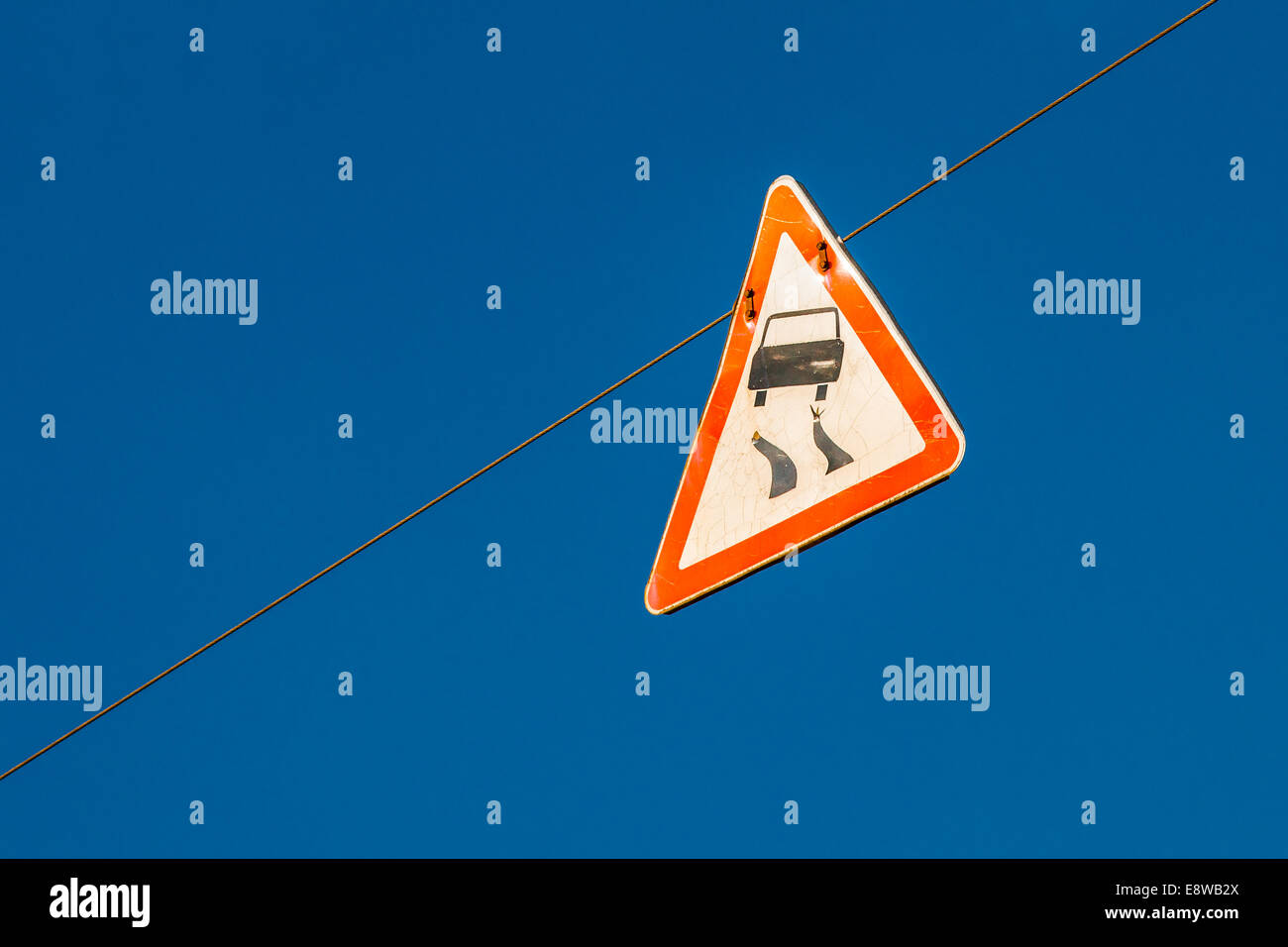 Be Prepared For Stunt Driving. A warning road sign hanging on a wire rope high in the blue sky - Stock Image