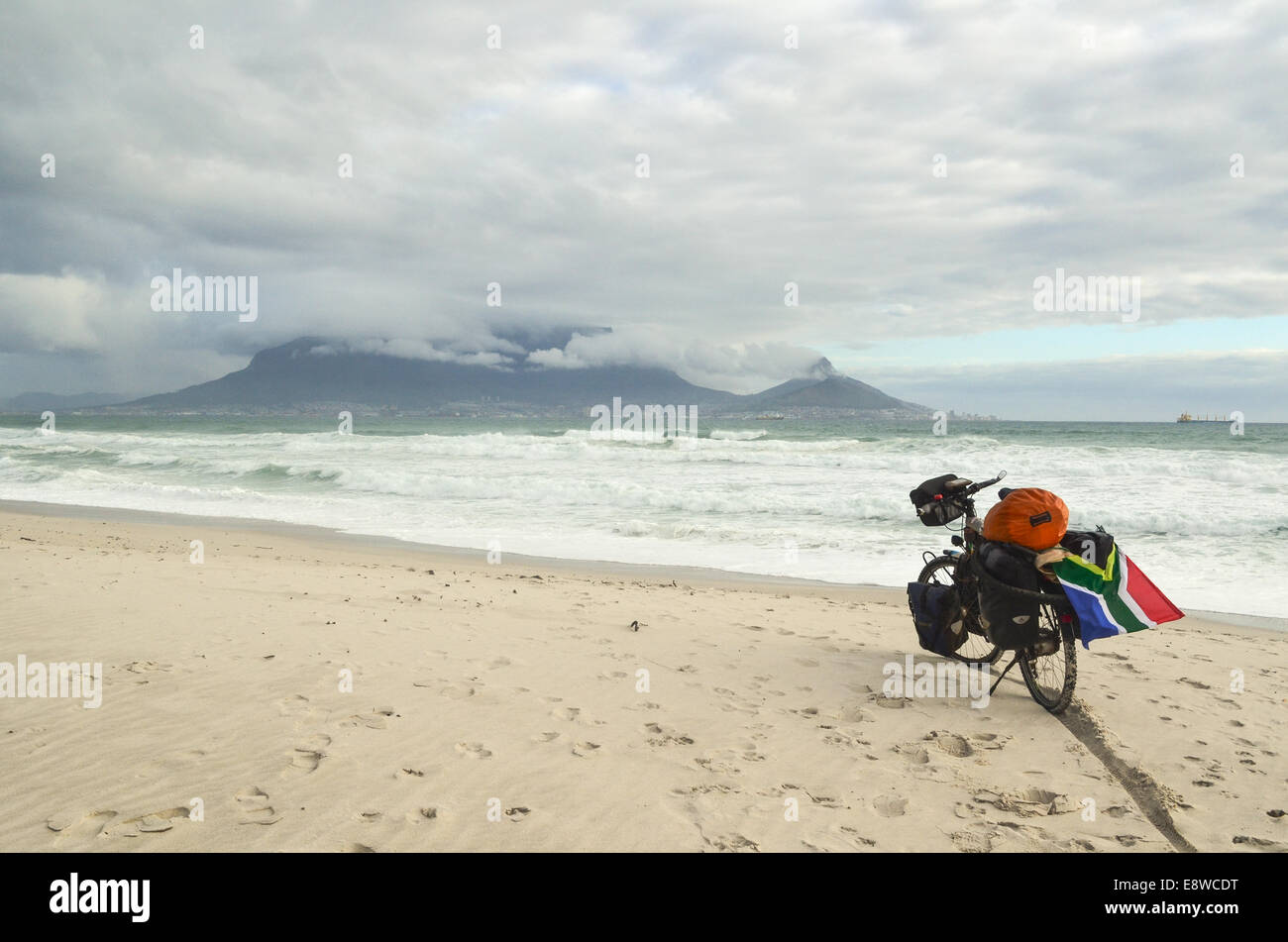 Cycle touring in Africa, a touring bicycle on the beach in Cape Town, South Africa, with cloudy skies, Table Mountain - Stock Image