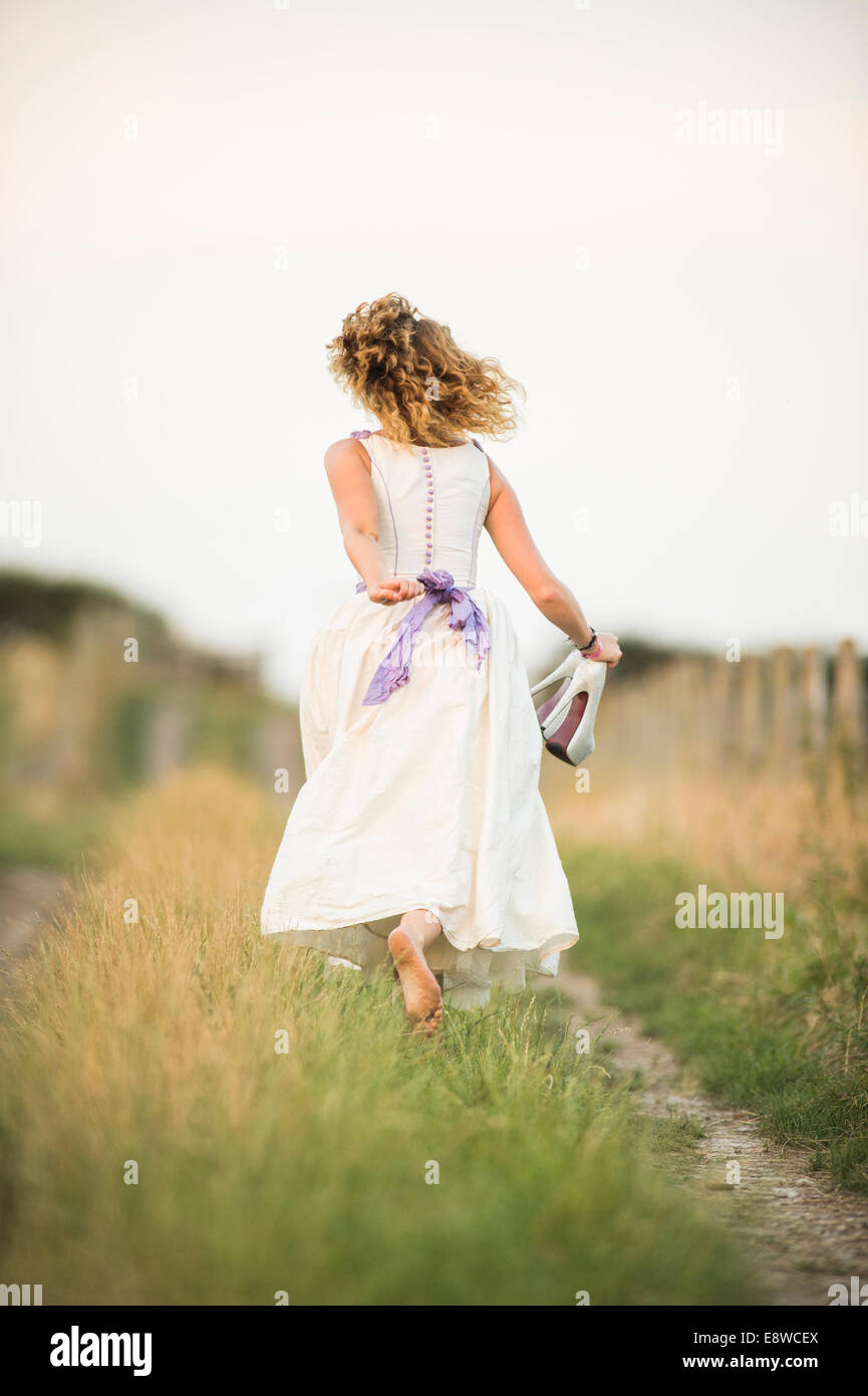 The runaway bride - a young woman girl in a wedding dress running barefoot away down a deserted country lane, summer Stock Photo