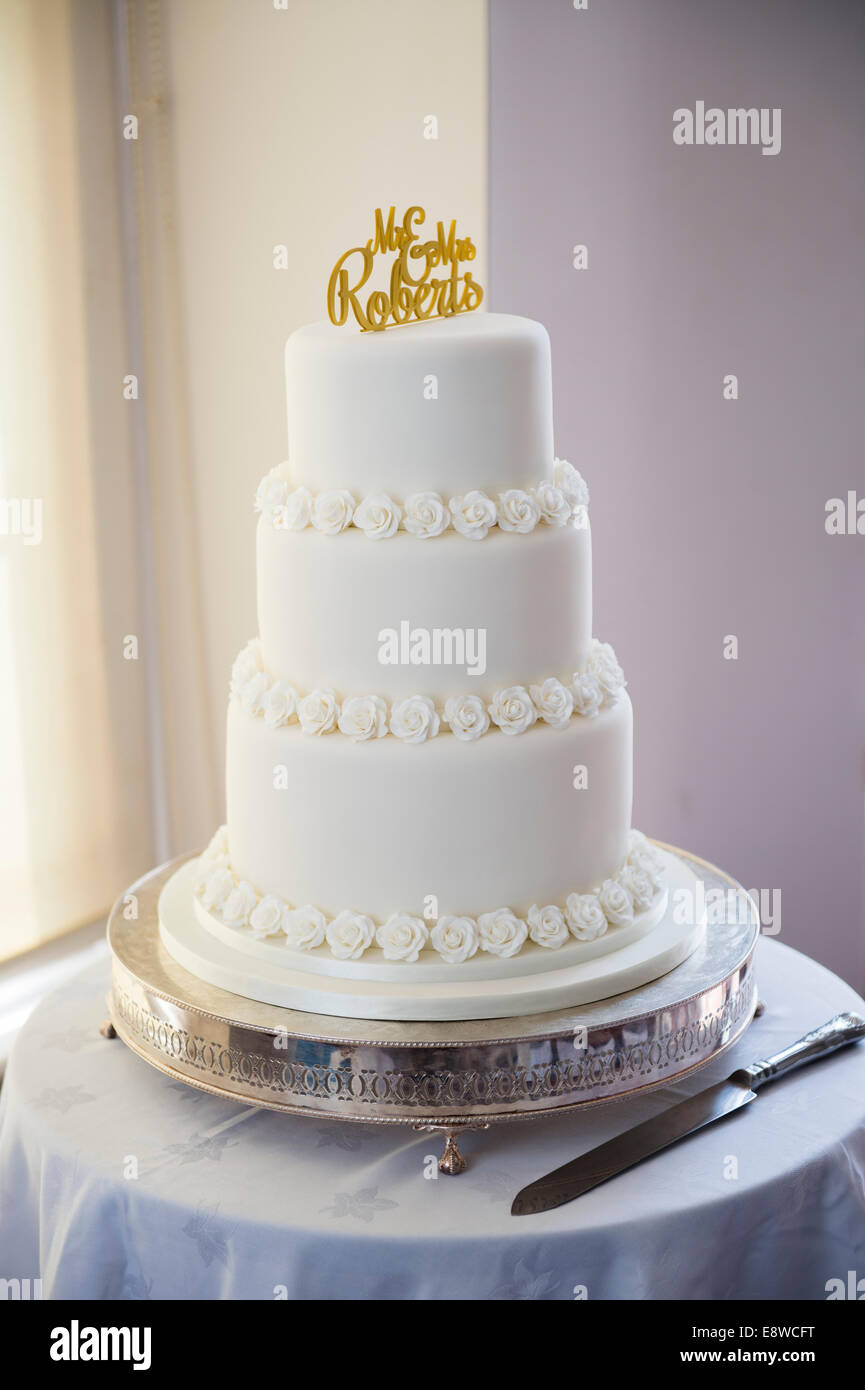 A simple traditional white icing covered three tier cake on wedding ...