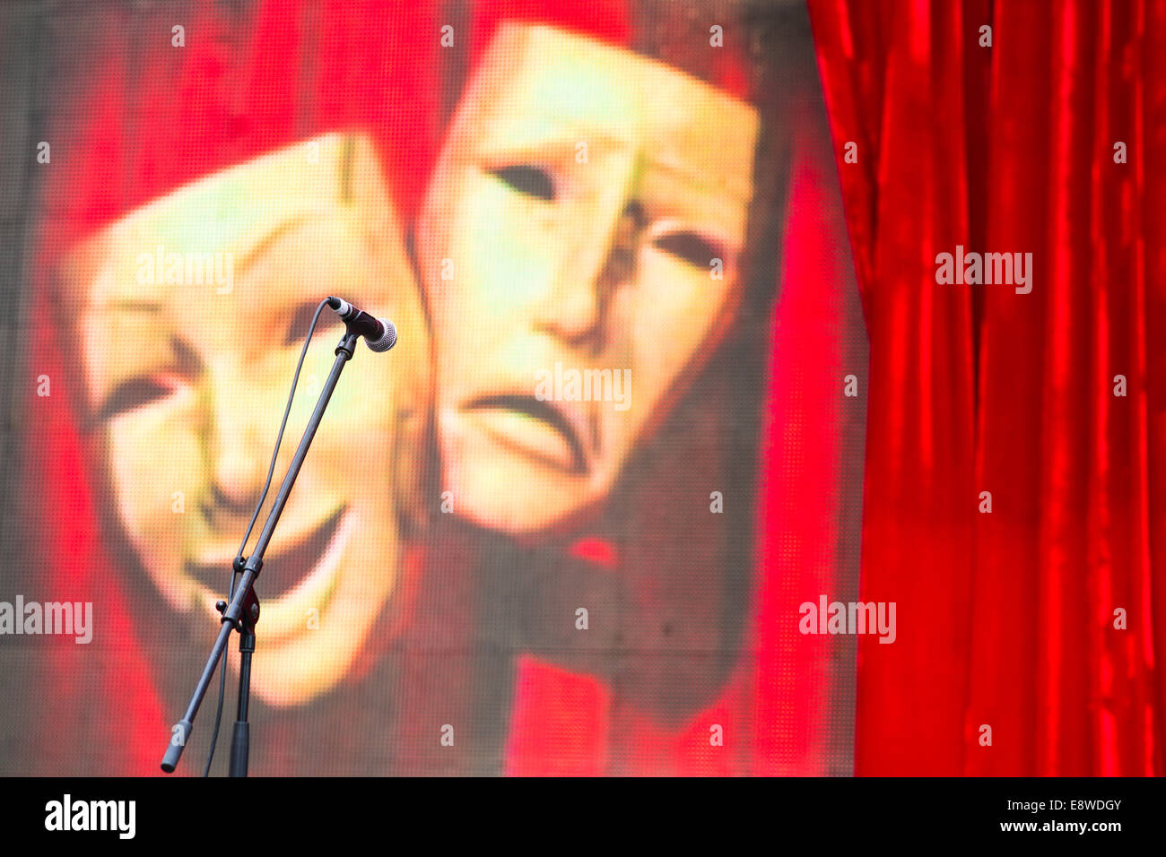 Masks. Theatrical masks, red curtain and microphone on an empty stage before the beginning of a performance - Stock Image