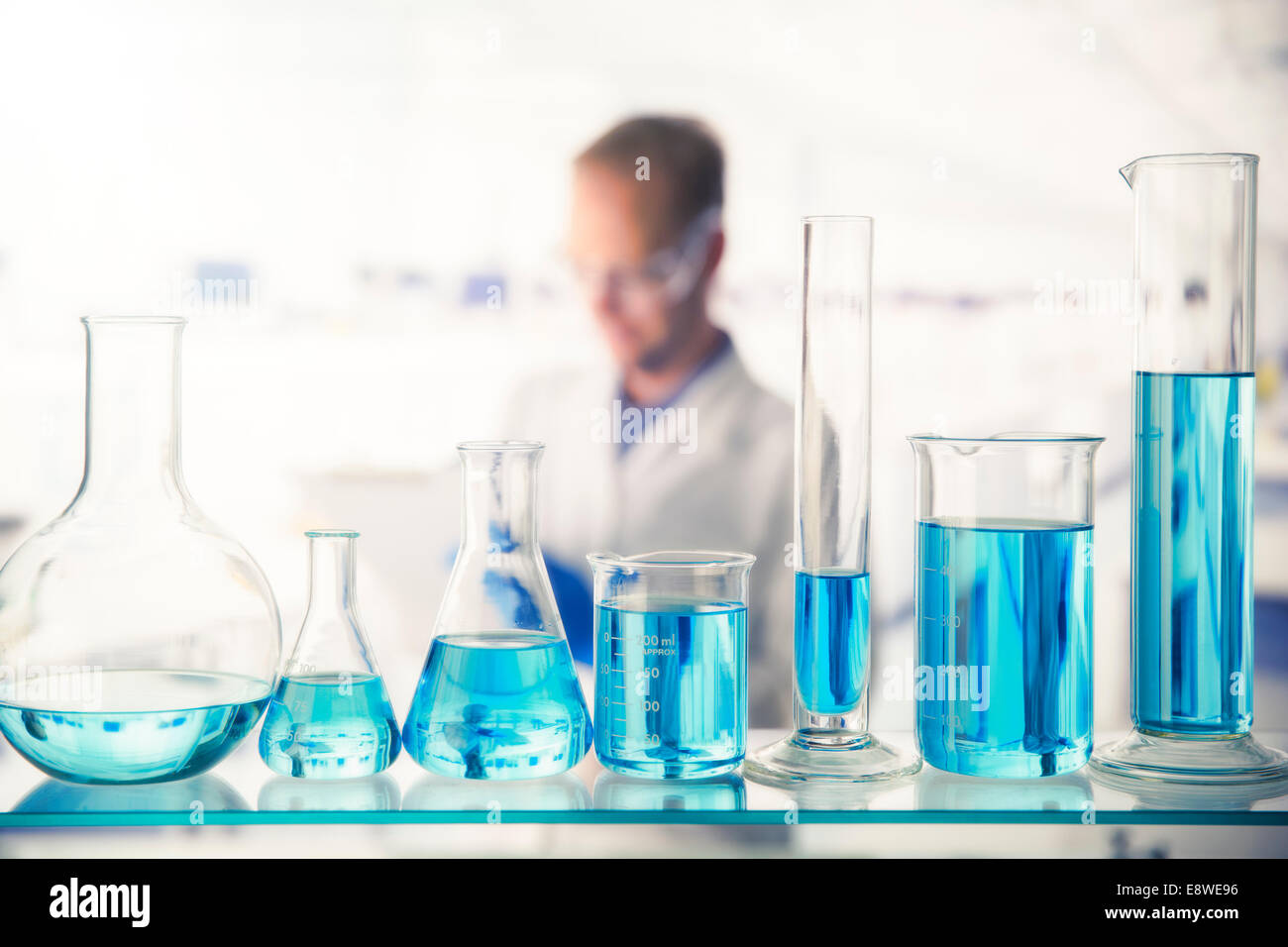 Close up of various solutions in beakers on shelf in lab Stock Photo