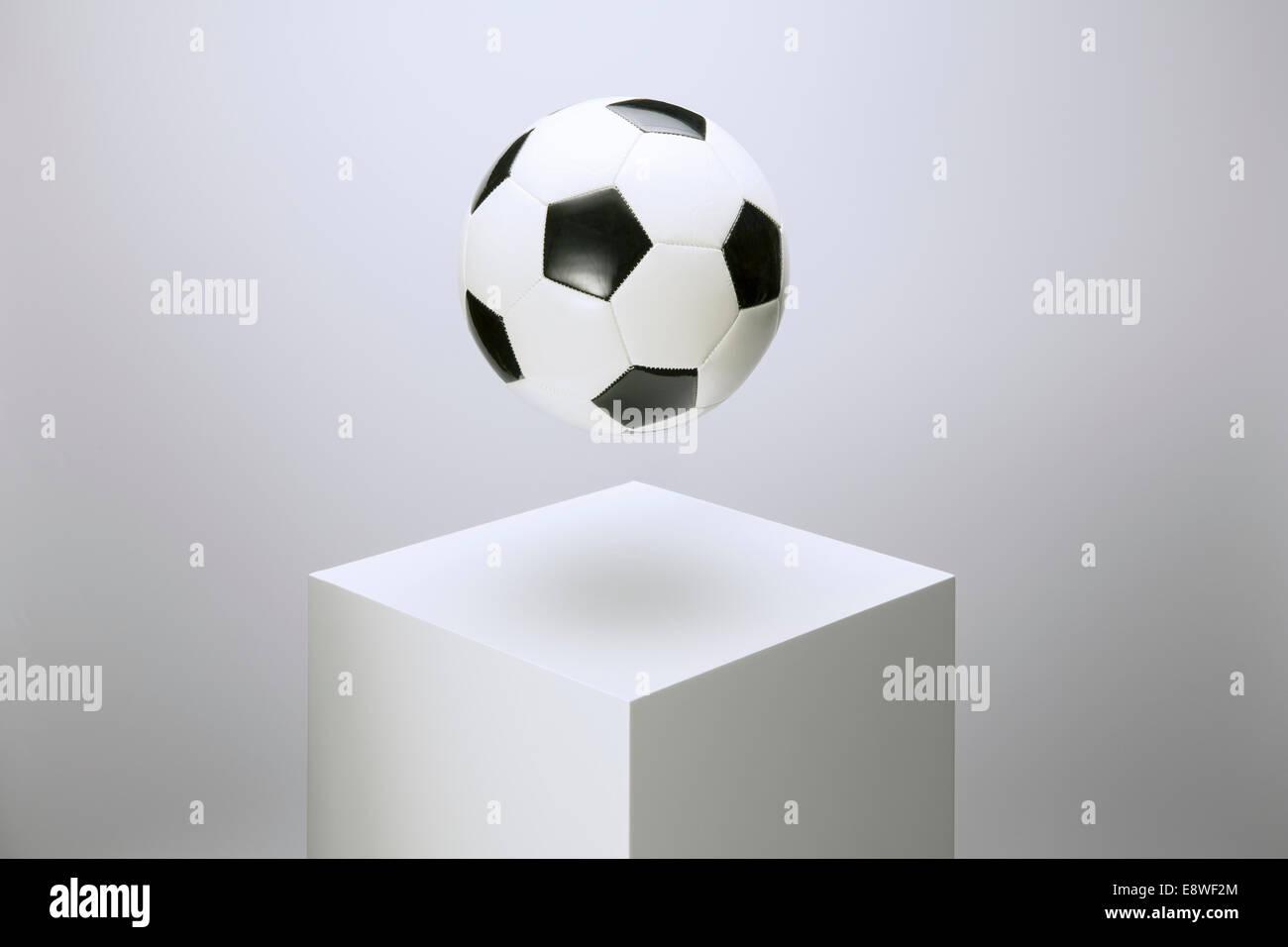 Soccer ball hovering over pedestal - Stock Image