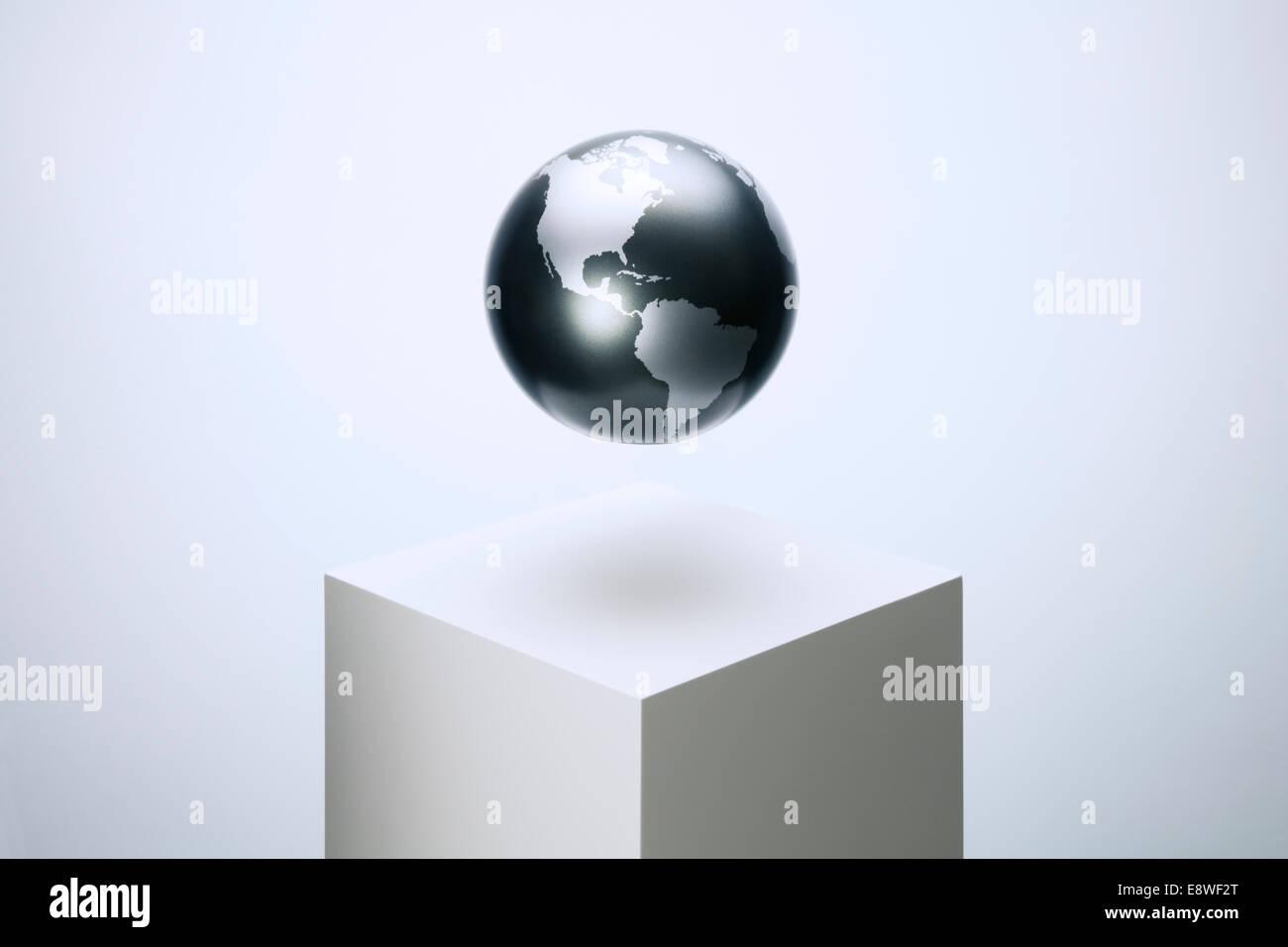 Globe hovering over pedestal - Stock Image