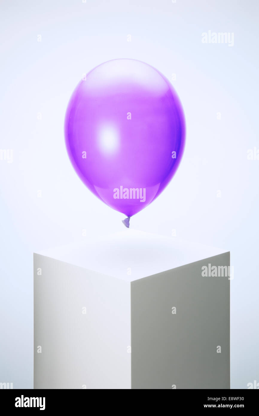 Purple balloon hovering over pedestal - Stock Image