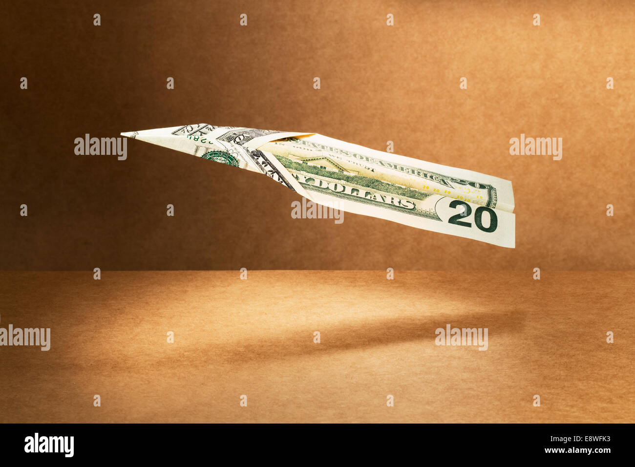20 dollar bill folded into paper airplane - Stock Image