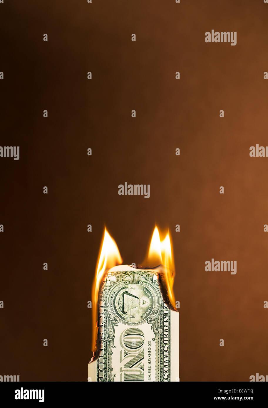 Folded dollar bill burning - Stock Image