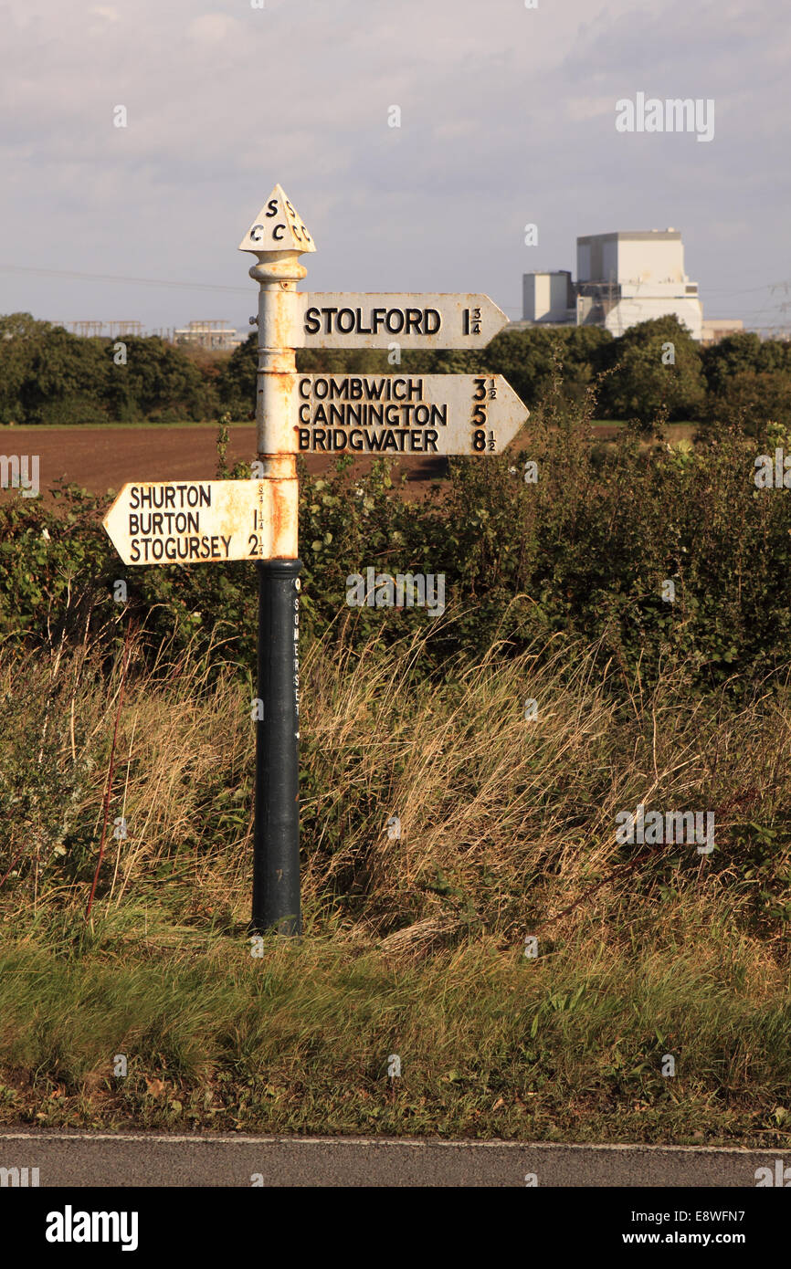 Hinkley Point nuclear power station in background with old road sign pointing to local villages Shurton Burton Stolford Stock Photo