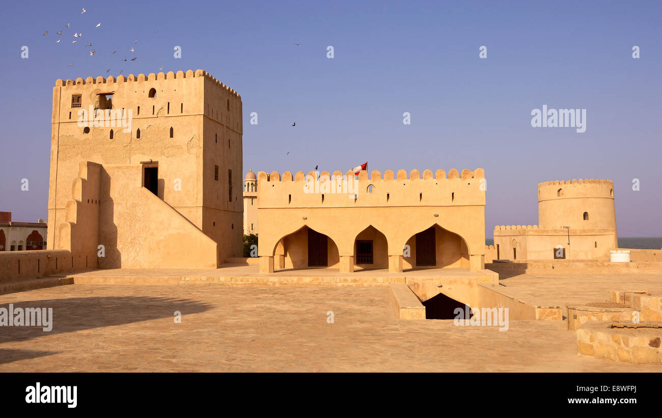 Pigeons fly over a tower at the castle in the market town of As Suwayq, in the Sultanate of Oman. - Stock Image