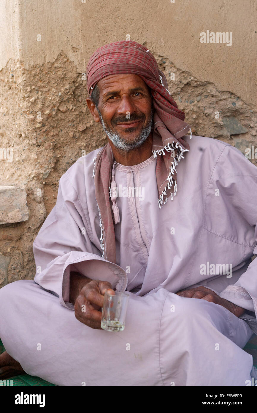 An Omani man, wearing a traditional headcloth, enjoying a glass of tea at the castle in the market town of As Suwayq - Stock Image