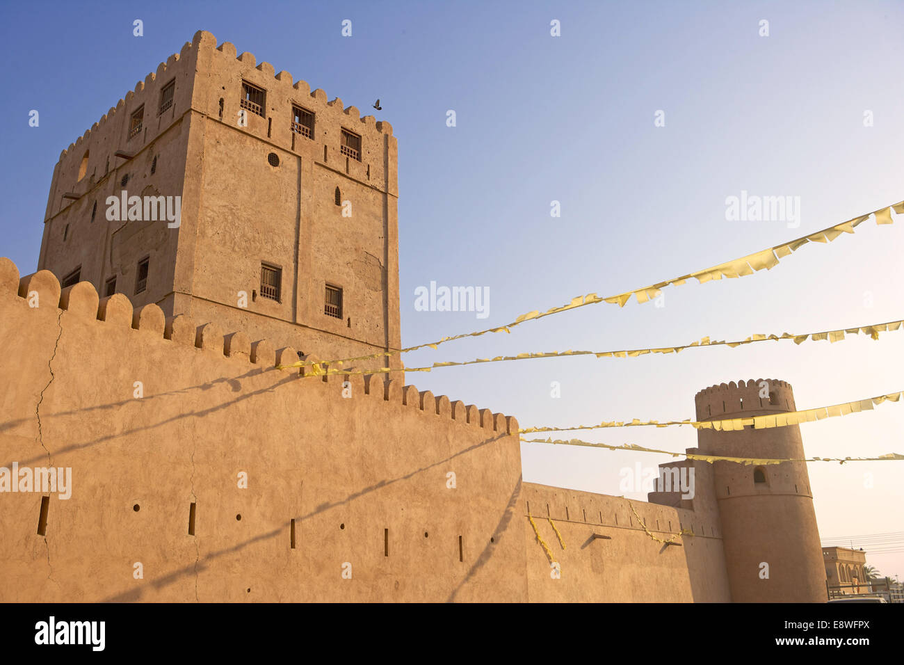 Festive bunting hanging from the castle in the market town of As Suwayq, in the Sultanate of Oman. - Stock Image