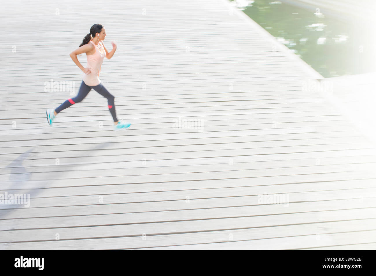 Woman running through city streets - Stock Image
