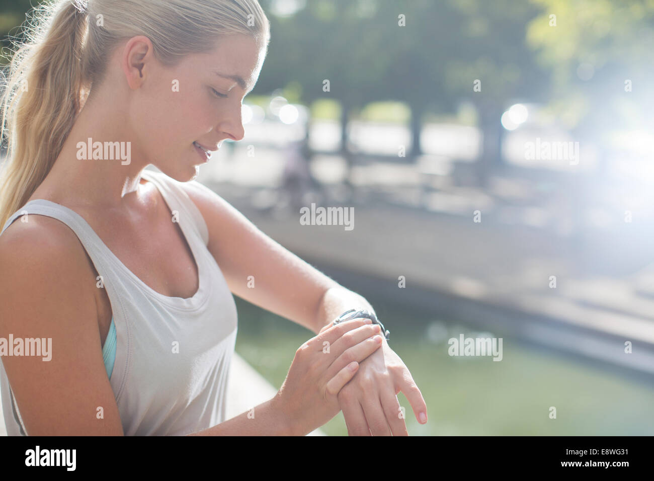 Woman looking at watch before exercising on city street - Stock Image