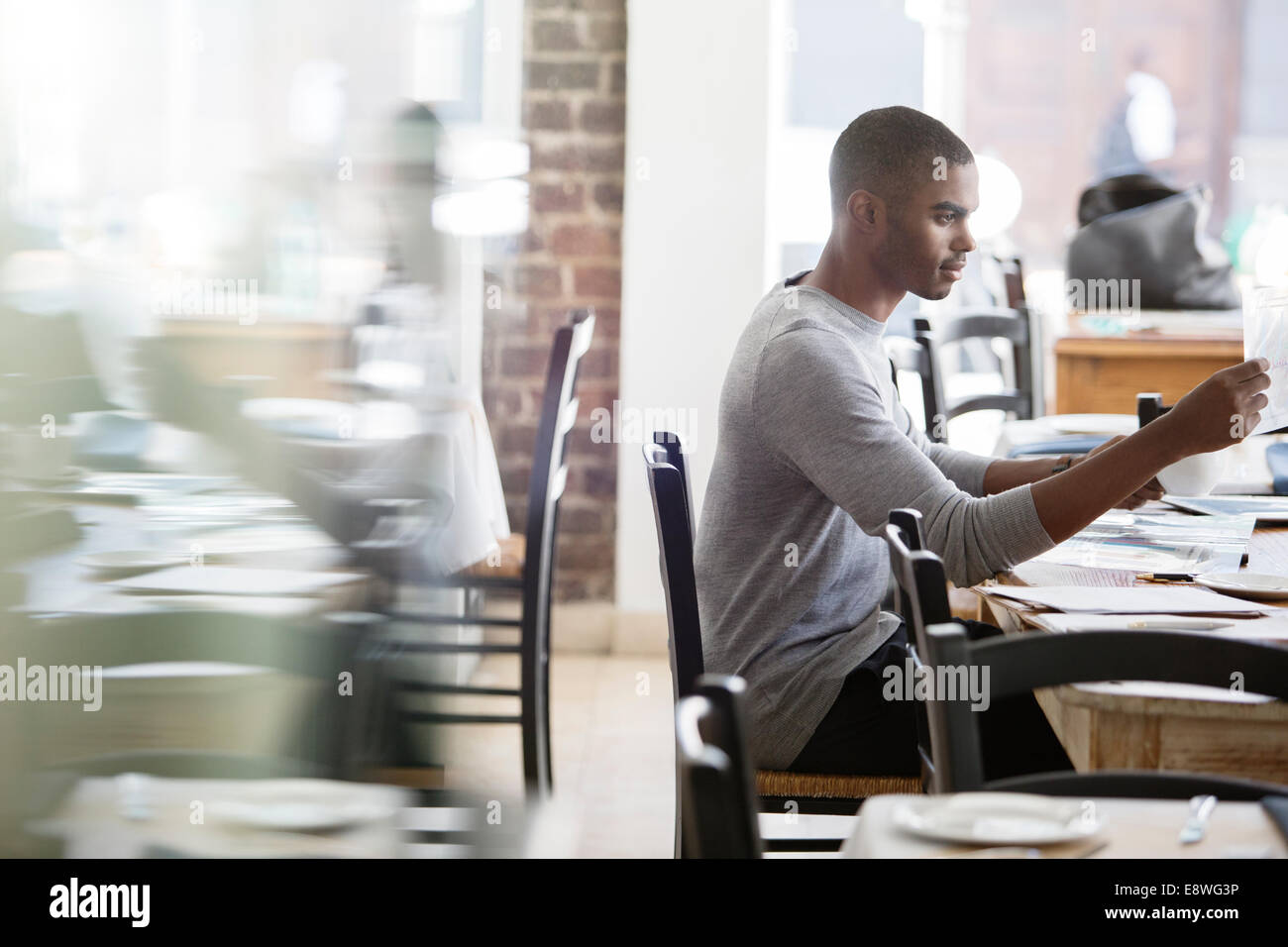 Businessman looking through documents in cafe - Stock Image