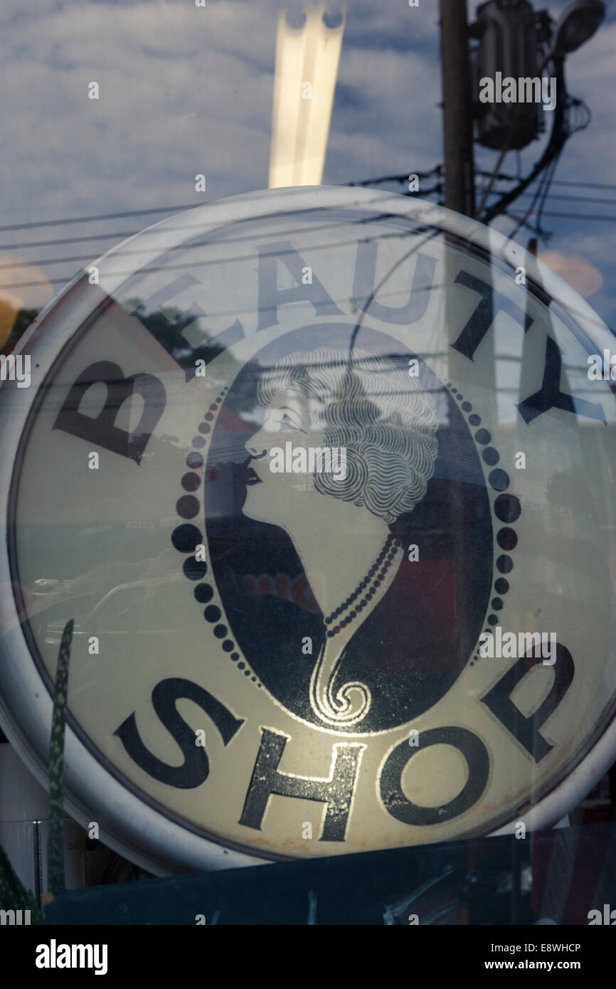 Oval 'Beauty Shop' sign refection in glass window - Stock Image