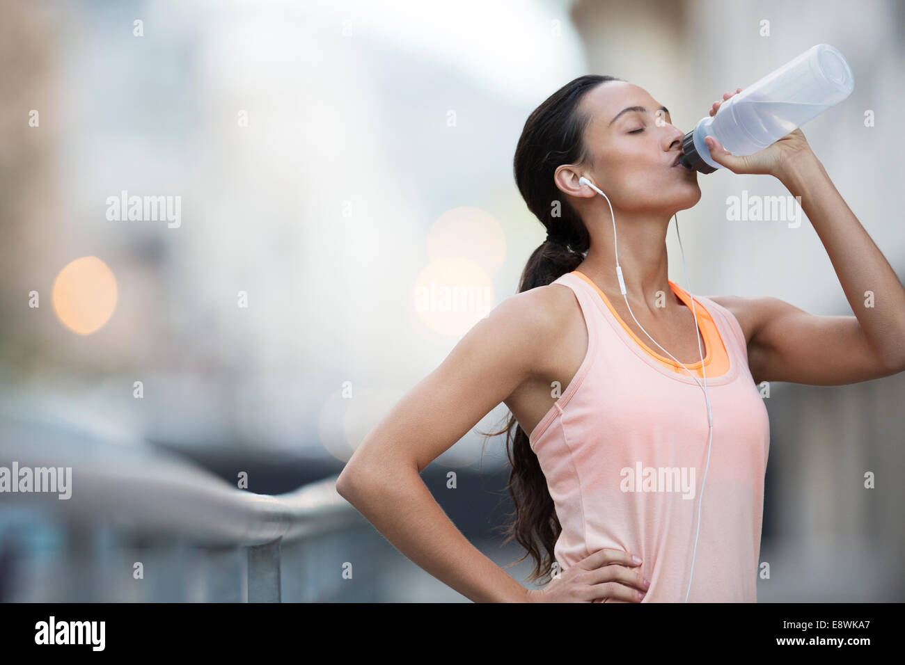 Woman drinking water after exercising on city street - Stock Image