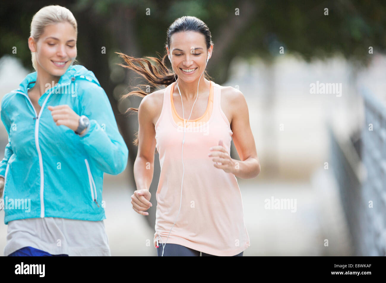 Women running through city streets together - Stock Image