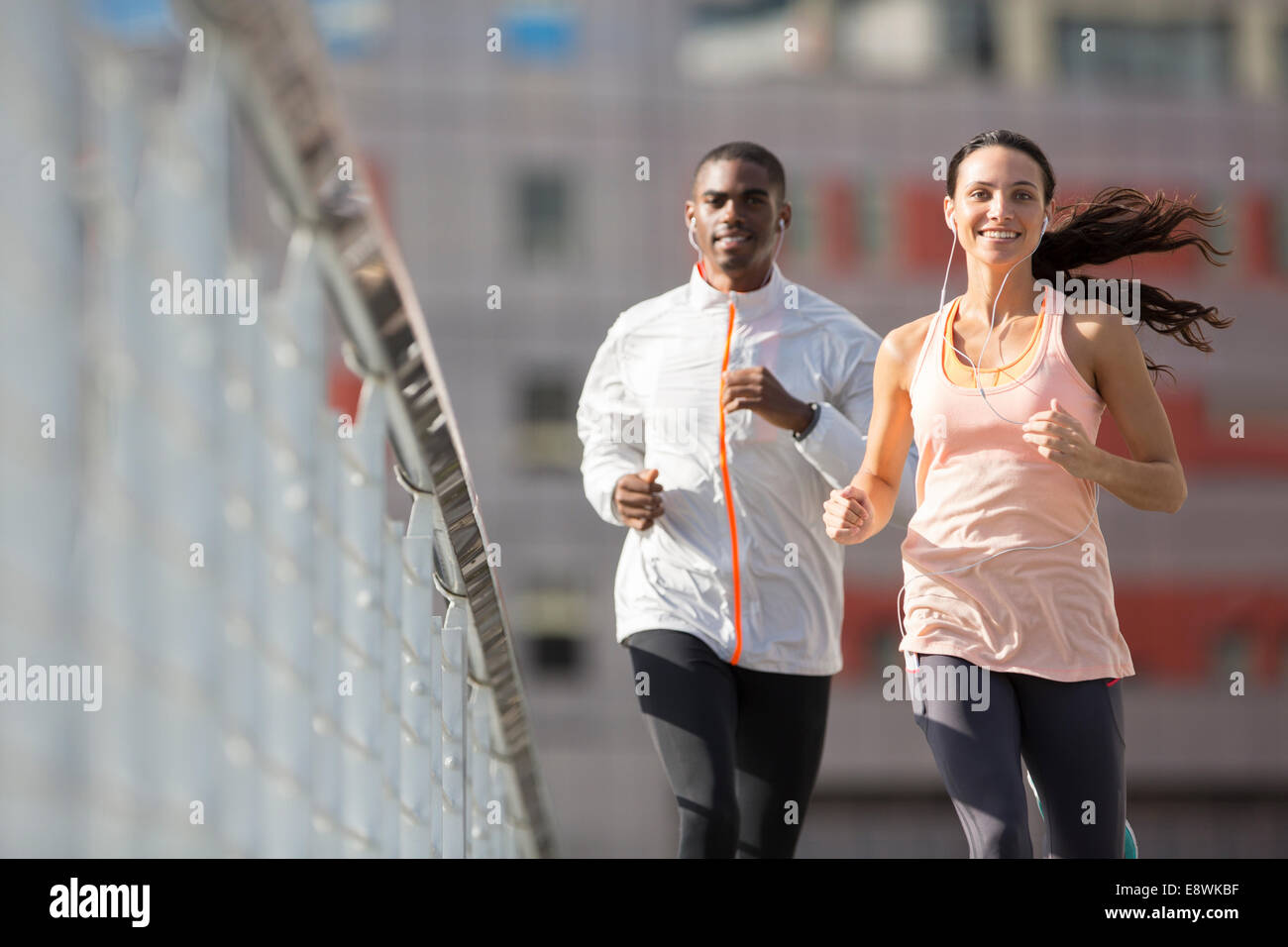 Friends running through city streets together Stock Photo