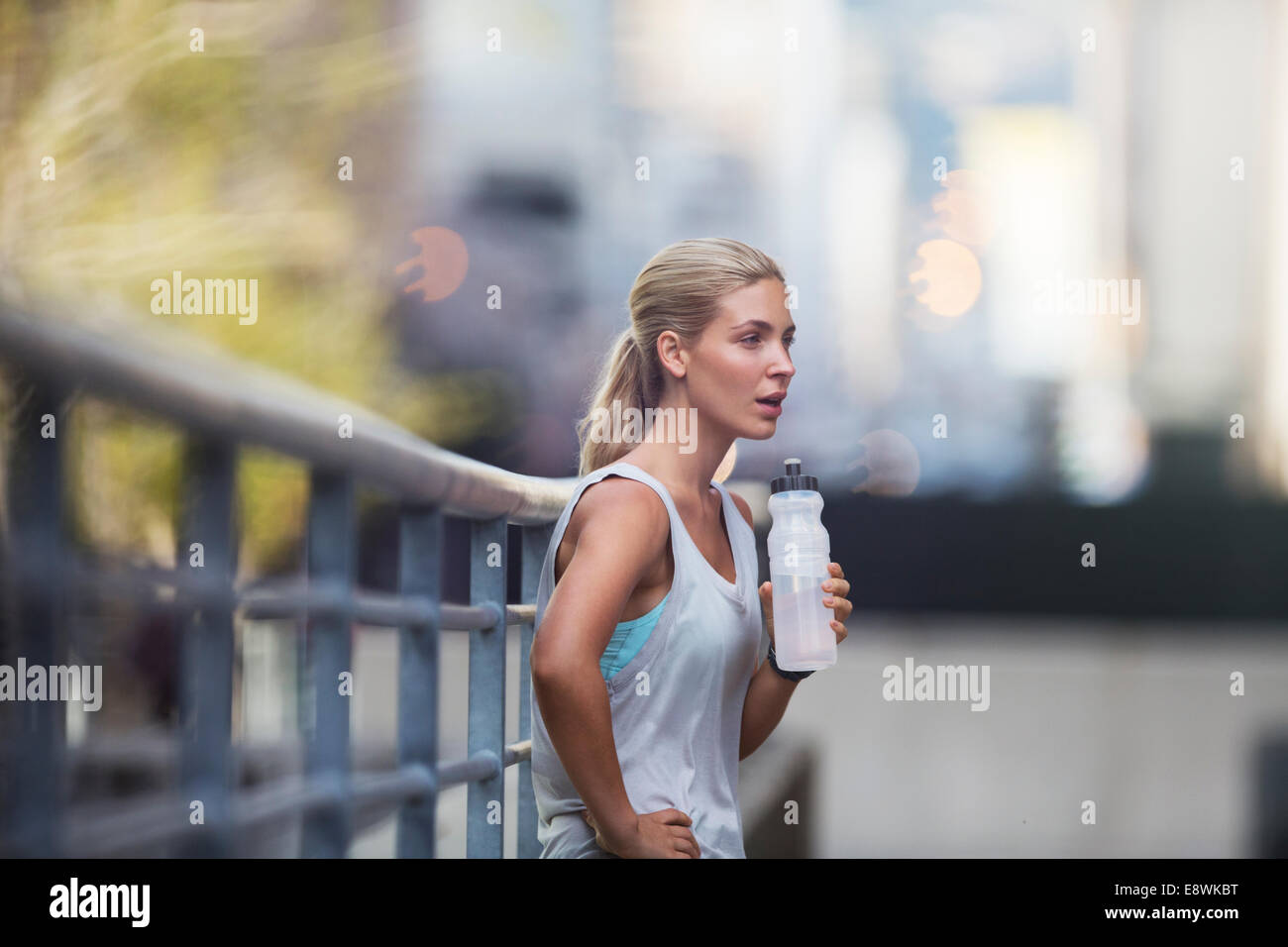 Woman resting after exercising on city street - Stock Image