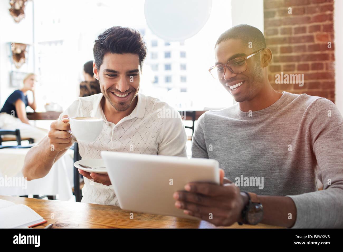 Businessmen using digital tablet in cafe - Stock Image