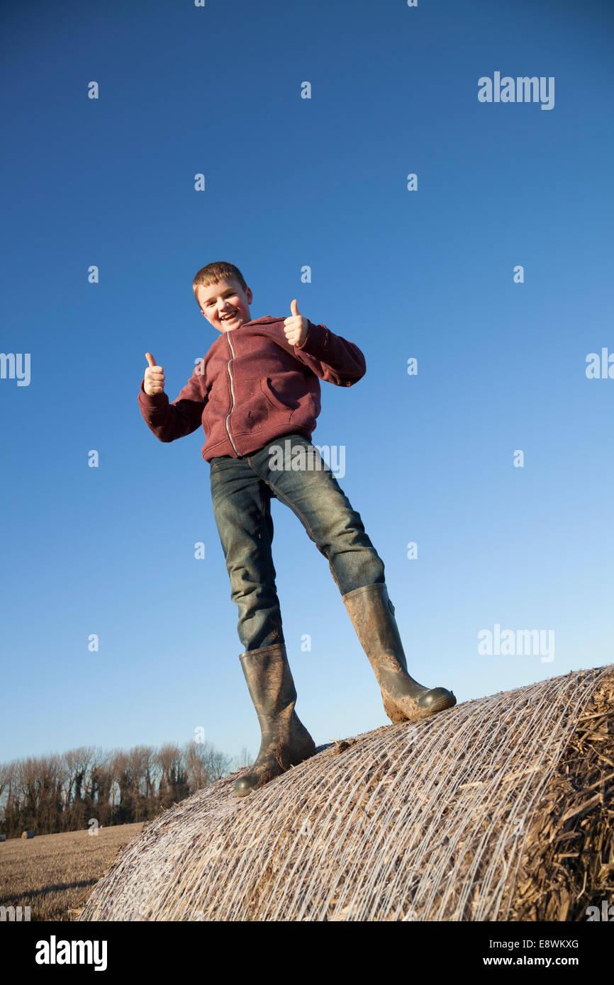 Smiling Farm Boy on a straw bale - Stock Image