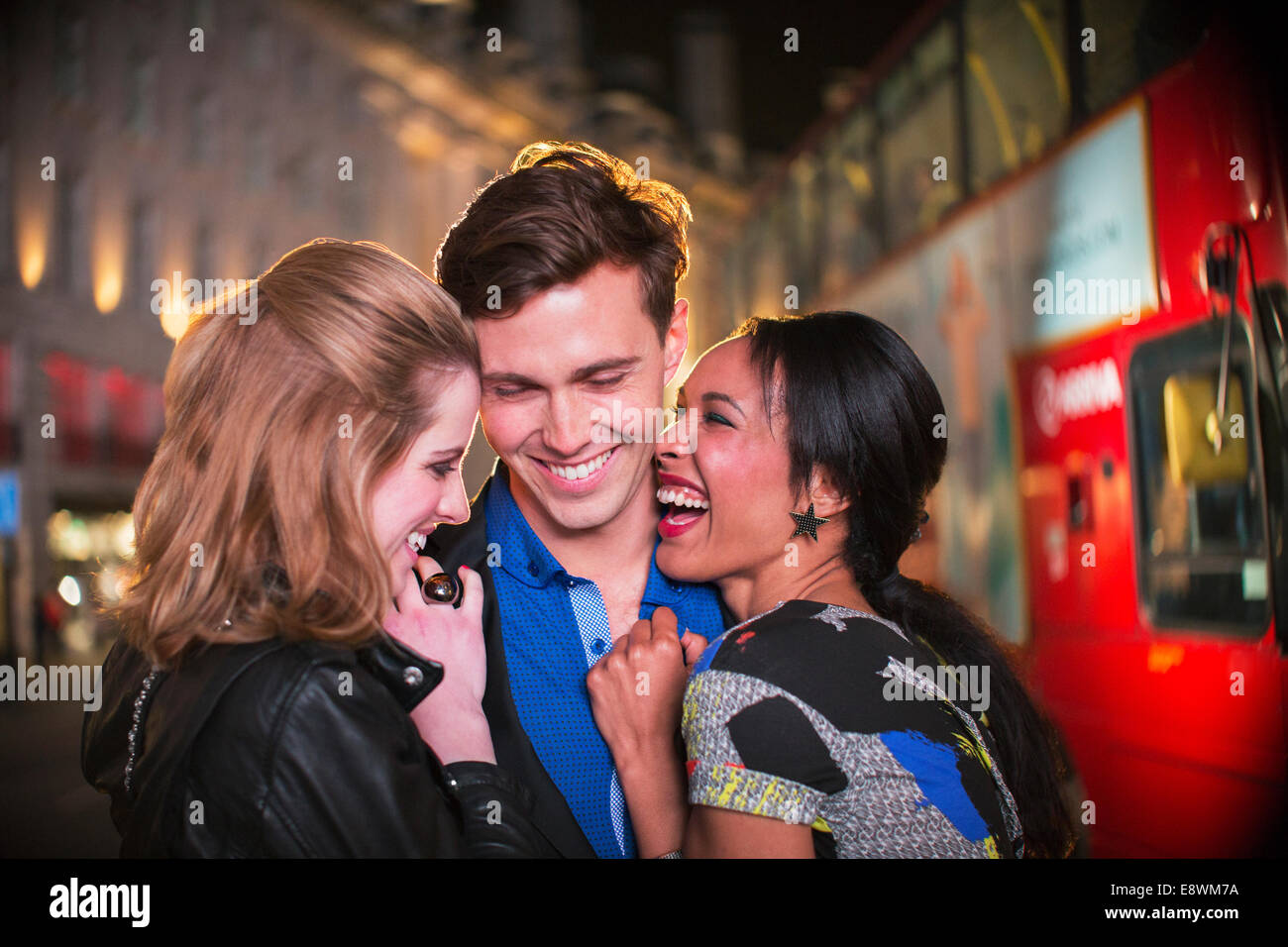 Friends hugging on city street at night - Stock Image