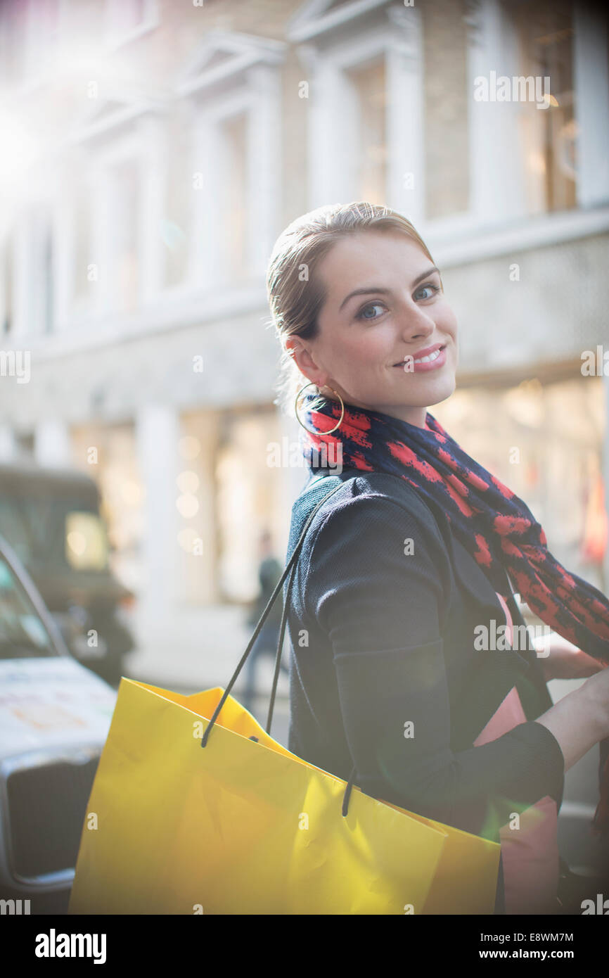 Woman with shopping bag crossing city street - Stock Image