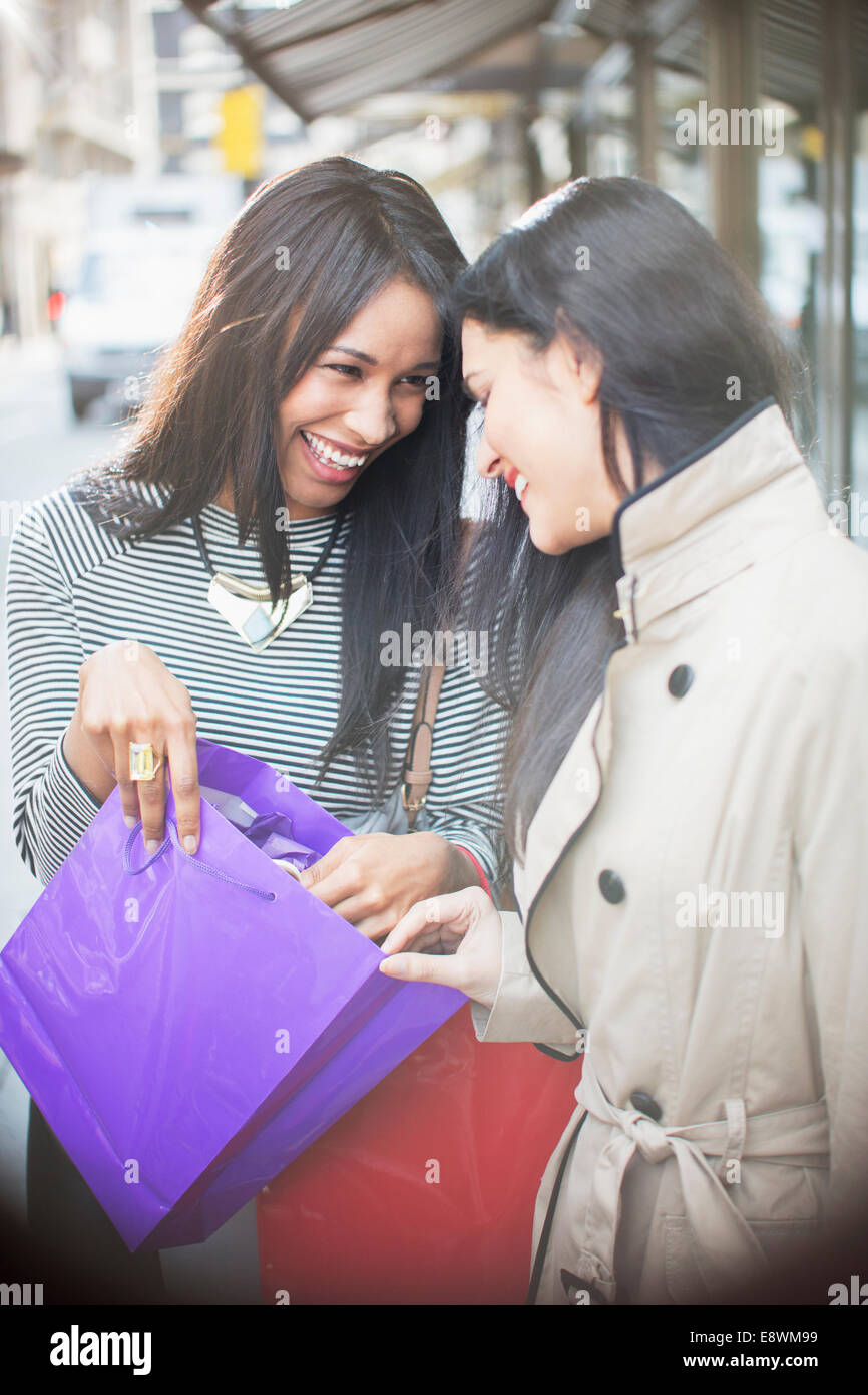 Women looking through shopping bag together on city street - Stock Image