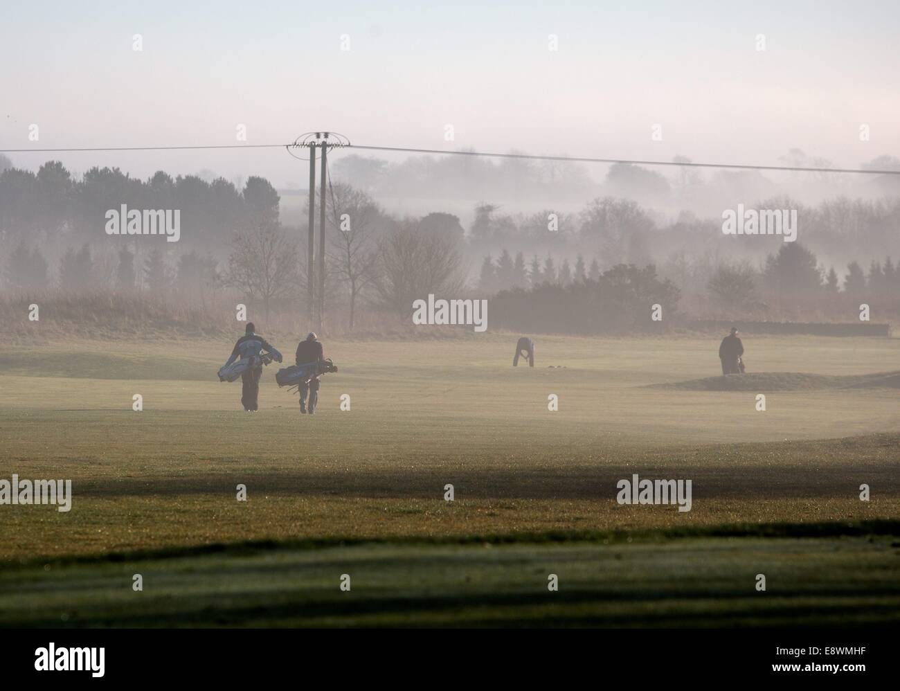 Golfers at Minchinhampton Golf Club enjoy the early morning sunshine, Minchinhampton, Gloucestershire. 19 Jan 2014 - Stock Image
