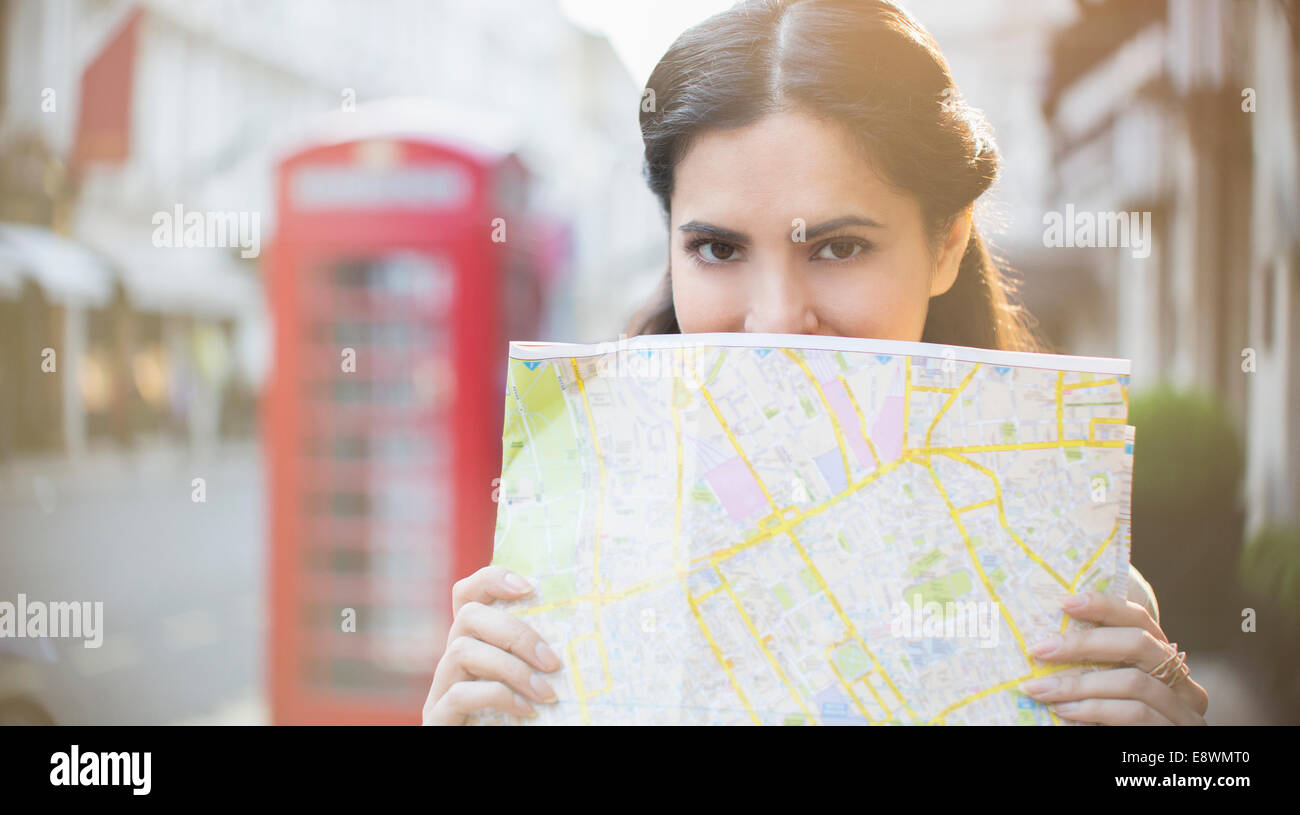 Woman holding map on city street - Stock Image
