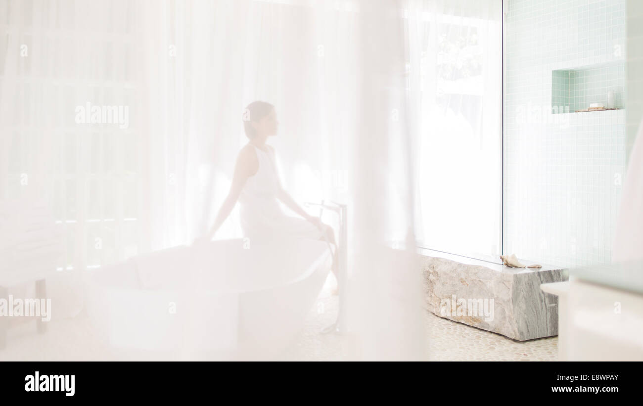 Woman in modern bathroom viewed through sheer curtain - Stock Image