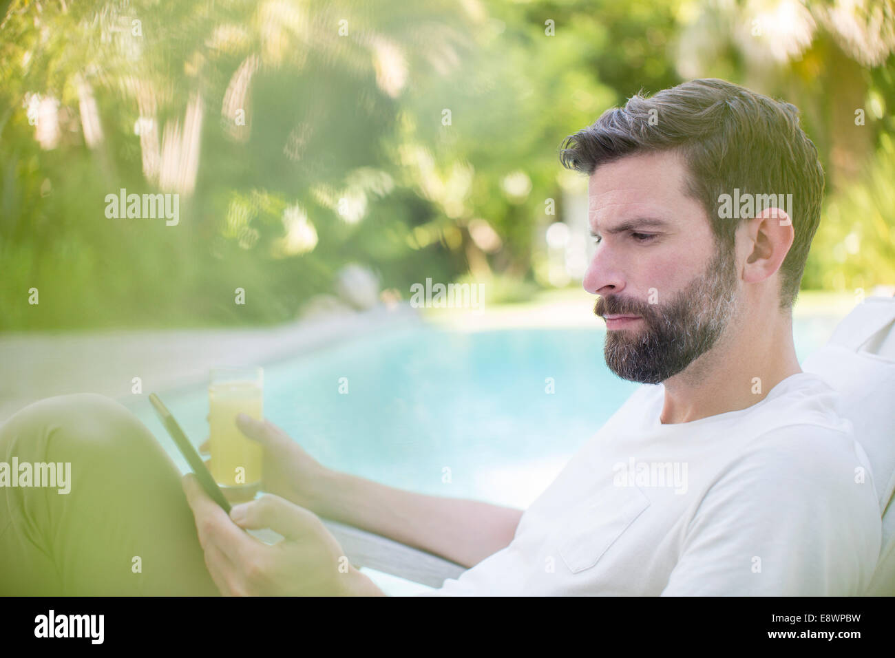 Man using digital tablet and drinking juice by swimming pool - Stock Image